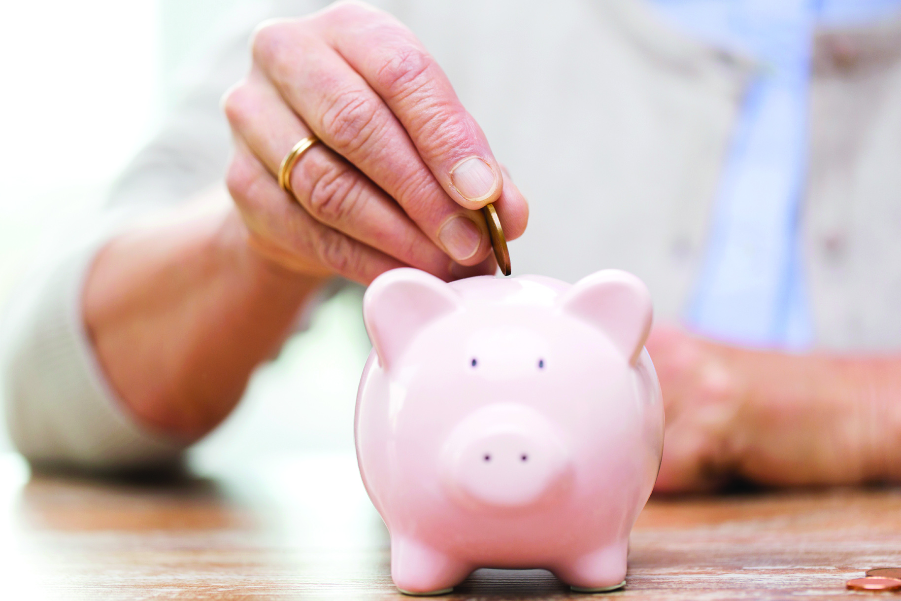 savings, money, annuity insurance, retirement and people concept - close up of senior woman hand putting coin into piggy bank
